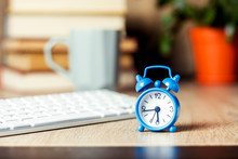 Alarm Clock And Keyboard On The Office Desk. Office Concept, Work Day, Hourly Pay, Work Schedule.