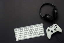 Keyboard, Gamepad And Headphones On A Black Background. The Concept Of The Game On The Console, Gaming. Flat Lay, Top View.