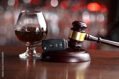 Poster de jardin Bar The concept of a DUI. Law hammer, alcohol and car keys on wooden table, dark background