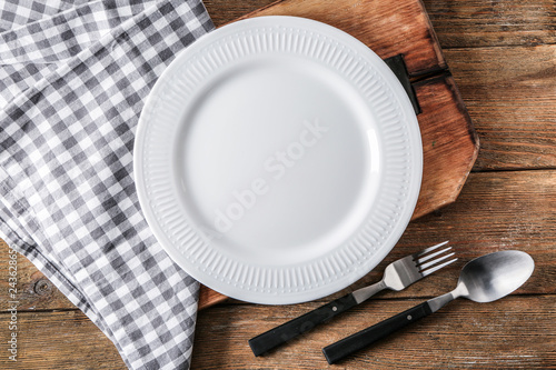 Fotografia Empty ceramic plate with cutlery, napkin and board on wooden background