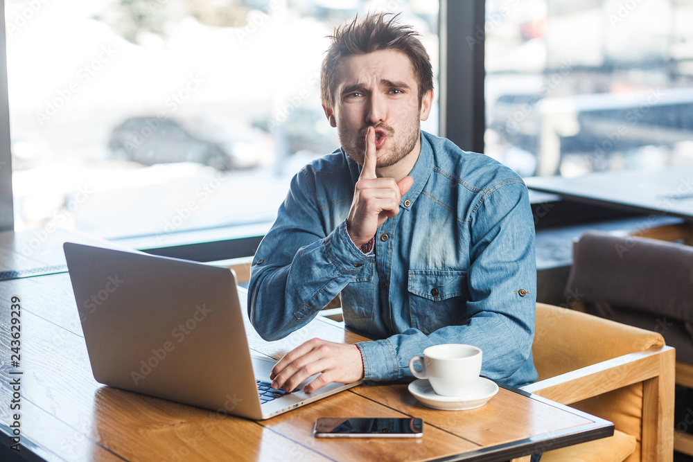 Fototapeta Be quiet please! Portrait of handsome severe bearded young freelancer in blue jeans shirt are sitting in cafe and working on laptop, lean finger on mouth showing silence sign, looking at camera.