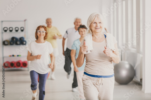 Fotografija  Smiling senior fitness instruct exercising with group of active seniors