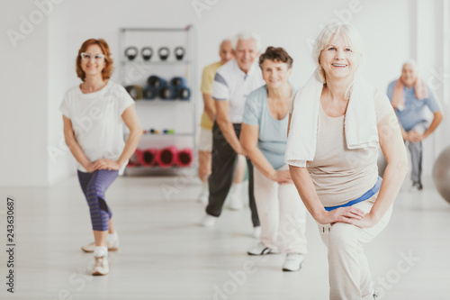 Fotografie, Obraz  Smiling senior woman exercising with group of active seniors in fitness center