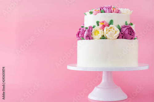 Photo  Two-tiered white wedding cake decorated with color cream flowers on a pink background