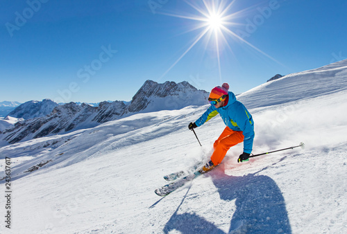 Deurstickers Wintersporten Skier skiing downhill in high mountains
