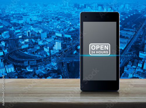 Fotografija  Open 24 hours icon on modern smart mobile phone screen on wooden table over city