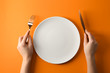 canvas print picture - Female hands with cutlery and empty plate on color background