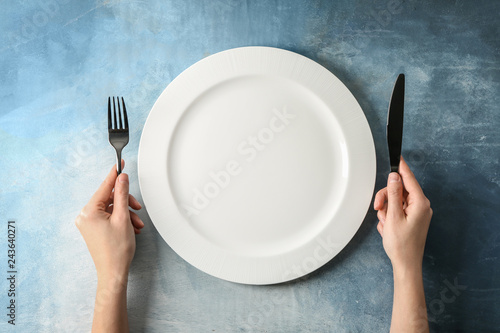 Valokuva  Female hands with cutlery and empty plate on color background