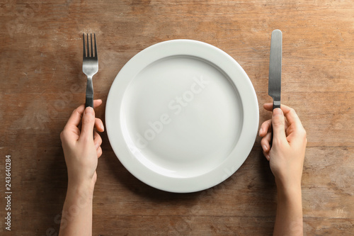 Photo  Female hands with cutlery and empty plate on wooden background