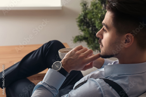 Fotografiet  Stylish handsome man drinking coffee at home