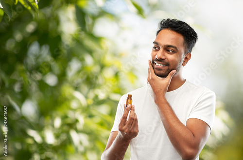 Photo grooming and people concept - smiling young indian man applying lotion or beard