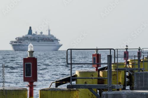Foto op Plexiglas Poort NAVIGATION LIGHT - Infrastructure of sea port in Kolobrzeg and a cruise ship in the roadstead