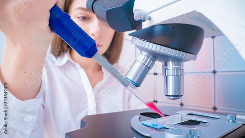 Fototapeta  Young woman technician is examining a histological sample, a biopsy in the labor