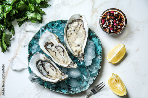 Plate with tasty cold oysters on light table Fototapeta
