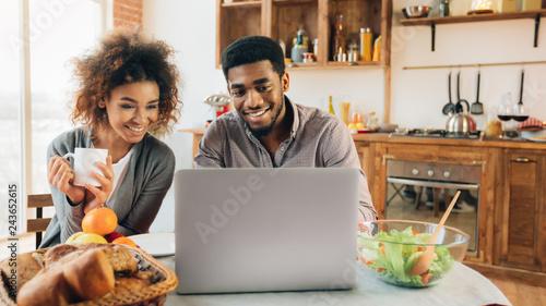 Fotografía  African-american man working on laptop in kitchen