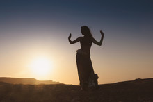 Woman Dancing To The Famous Arab Belly Dance. With Sunset In The Arid Desert Plain Of Namibe. Africa. Angola.