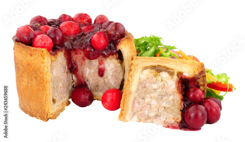 Pork pie topped with cranberries with fresh salad isolated on a white background