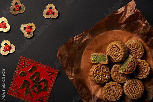 top view of traditional mooncakes with chinese talismans isolated on black