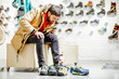 canvas print picture - Man in winter jacket trying shoes for mountain hiking sitting in the fitting room of the modern sports shop