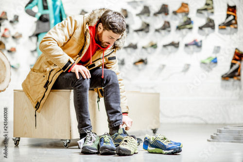 Man in winter jacket trying shoes for mountain hiking sitting in the fitting roo Fotobehang