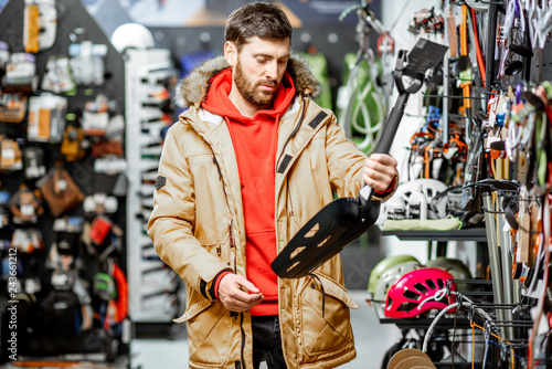 Fotografía  Man in winter jacket choosing mountaineer equipment holding snow shovel in the s