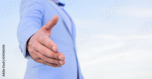 Cuadros en Lienzo Hand of businessman offer hand for handshake blue sky background