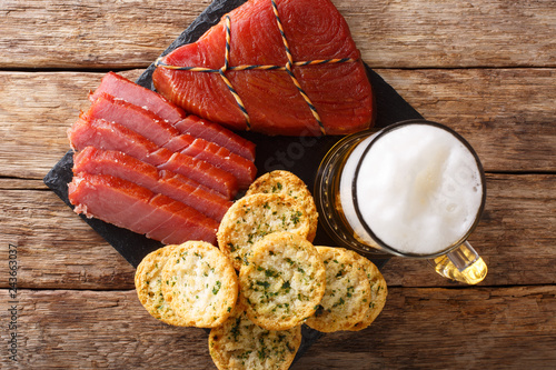 Foamy beer served with smoked tuna and toast with garlic and greens closeup. horizontal top view