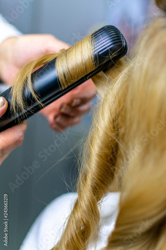 Foto op Aluminium Ree Close-up photo professional hairdresser uses flat iron for making curls on beautiful blonde hair