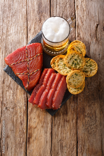 Light beer with foam, smoked tuna and toast with garlic and greens closeup. Vertical top view