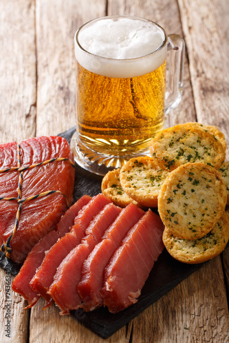 Golden beer glass served with smoked tuna and toasts with garlic and herbs close-up. vertical