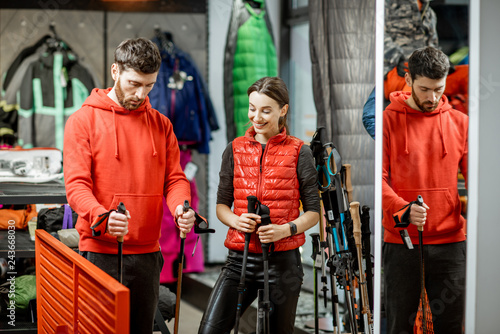 Türaufkleber Phantasie Man and woman choosing traveling equipment looking on the hiking sticks in the shop