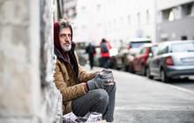 Homeless Beggar Man Sitting Outdoors In City Asking For Money Donation.