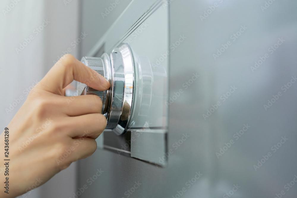 Fototapeta Hand of businesswoman opening code lock of her safe
