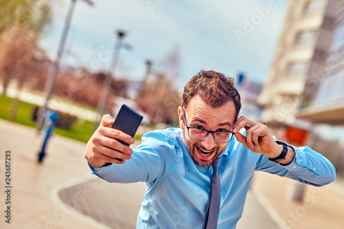Fotografie, Obraz  Funny businessman with thumbs up while using smartphone outdoors.