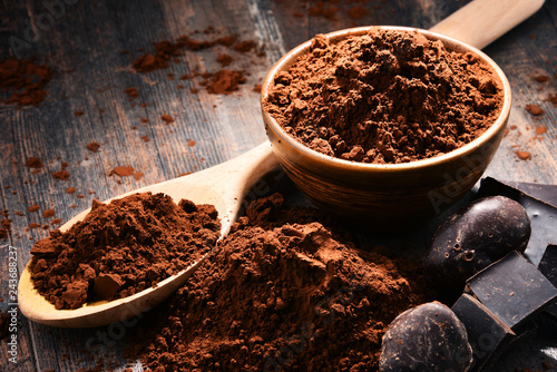 Composition with bowl of cocoa powder on wooden table