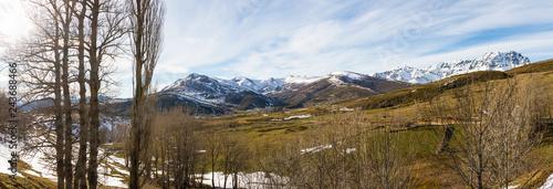 Vista panorámica de paisaje invernal con nieve. Con praderas en la ladera de una sierra de montañas nevadas y el sol penetrando entre los árboles