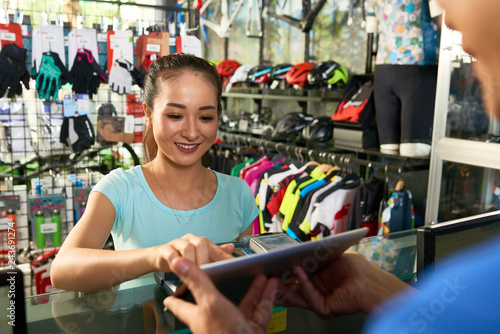 Female sports store customer entering payment details into app on tablet computer in hands of cashier