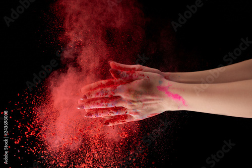 Fotografie, Obraz  cropped view of adult woman holding red holi powder and clapping on black backgr
