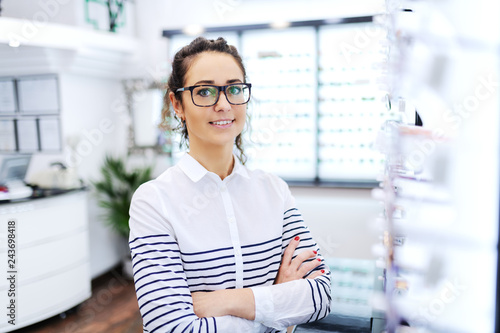 Young Caucasian woman with brown hair holding arms crossed and wearing eyeglasses while standing at optician.
