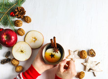 Woman's Hand Holding A Cup Of Apple Tea And Christmas Decorations