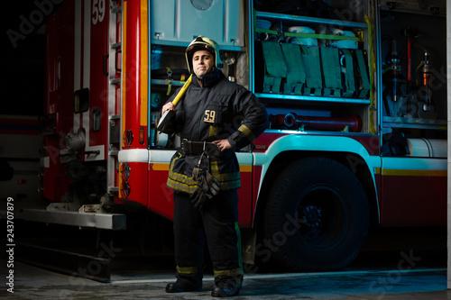 Full-length photo of firefighter man with pick near fire truck Fototapeta