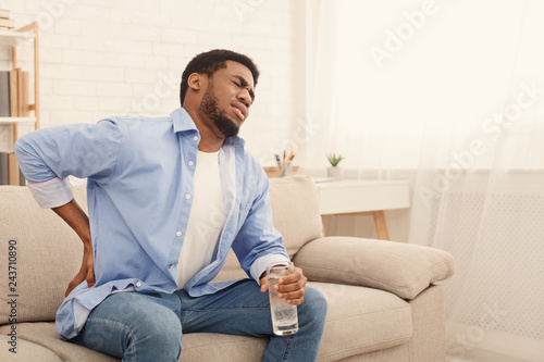 Fotografia  Young black man with back pain at home