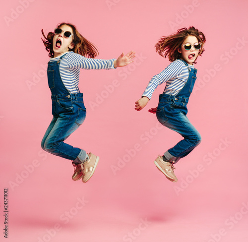 Fotografie, Obraz  Twin sisters jumping in fashion outfits