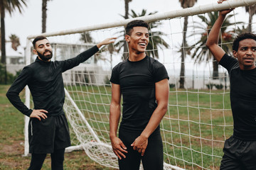 Footballers standing near the goalpost relaxing
