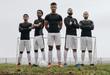 Leinwanddruck Bild - Footballers standing side by side on a soccer field