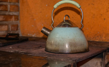 Old Steel Teapot On A Wood Burning Stove On The Farm.