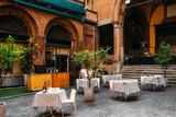 Fototapeta Uliczki - Old narrow street with tables of restaurant in Bologna, Emilia Romagna, Italy