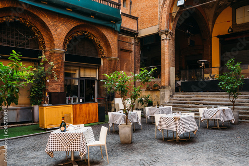 Fotografie, Tablou Old narrow street with tables of restaurant in Bologna, Emilia Romagna, Italy