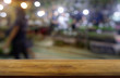 Empty dark wooden table in front of abstract blurred background of restaurant, shopping mall and people walking. can be used for display or montage your products - Image.