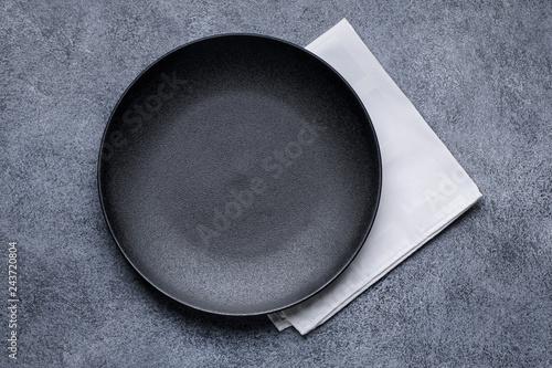 Fotografía Empty black plate and white napkin on gray concrete background